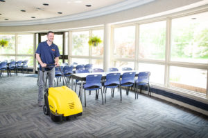 Smylies employee using industrial carpet cleaner